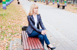 Woman in an autumn park sits on a bench Stock Image
