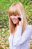 Woman in an autumn park with a telephone  in hands Stock Images