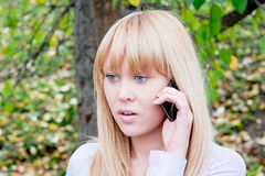 Woman in an autumn park with a telephone  in hands Stock Photo