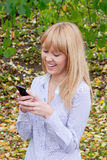 Woman in an autumn park with a telephone  in hands Royalty Free Stock Photography