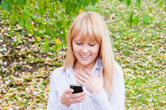 Woman in an autumn park with a telephone  in hands Stock Photography