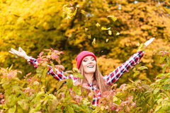 Woman in autumn park throwing leaves up in the air Royalty Free Stock Photo