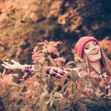 Woman in autumn park throwing leaves up in the air Stock Photo