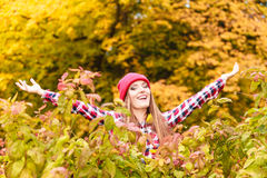 Woman in autumn park throwing leaves up in the air Royalty Free Stock Image