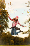 Woman in autumn park throwing leaves up jumping Royalty Free Stock Photography