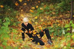 Woman in autumn park throws fallen leaves royalty free stock image