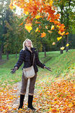 The woman in autumn park throws up red maple leaves in a sunny day. The beautiful woman in autumn park throws up red maple leaves stock photography