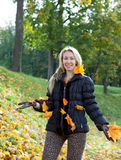 Woman in autumn park throws up red maple leaves in a sunny day. The beautiful woman in autumn park throws up red maple leaves royalty free stock photo