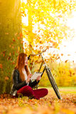Woman in autumn park using tablet computer reading. Technology internet modern lifestyle concept. Woman in autumn park using tablet computer reading. Girl with e Stock Photography