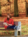Woman in autumn park using tablet computer reading. Technology internet modern lifestyle concept. Woman in autumn park using tablet computer reading. Girl with Royalty Free Stock Images