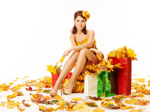 Woman autumn shopping in dress of maple leaves over white. Autumn woman with shopping bags in dress of maple leaves. White background Stock Photos