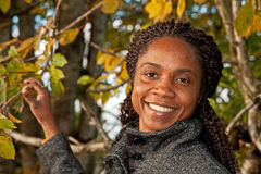 Woman among Autumn trees. Portrait of smiling attractive Angolan woman in the forest among the Autumn trees Stock Photos