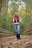 Woman on autumn walk. A happy young woman walking under colorful fall foliage holding leaves royalty free stock images