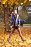 Woman at autumn walking on yellow leafs Royalty Free Stock Images