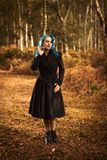 Woman In Autumn Woodland. Woman in vintage clothing and coat in woodland in the UK Royalty Free Stock Photos