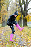 Woman in autumnal alley. Wearing pink rubber boots Stock Photos