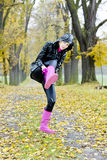 Woman in autumnal alley. Woman wearing rubber  boots in autumnal alley Royalty Free Stock Photos
