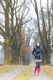 Woman in autumnal alley. Woman wearing rubber boots in autumnal alley Stock Photos