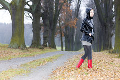 Woman in autumnal alley. Woman wearing rubber boots in autumnal alley Royalty Free Stock Photo