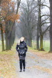 Woman in autumnal alley. Woman wearing black clothes and boots in autumnal alley Royalty Free Stock Photos