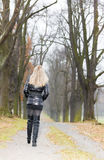 Woman in autumnal alley. Woman wearing black clothes and boots in autumnal alley Royalty Free Stock Images