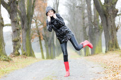 Woman in autumnal alley. Woman wearing rubber boots in autumnal alley Royalty Free Stock Images