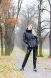 Woman in autumnal alley. Woman wearing black clothes and boots in autumnal alley Stock Image