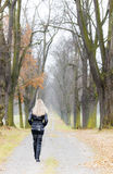 Woman in autumnal alley. Woman wearing black clothes and boots in autumnal alley Royalty Free Stock Photography