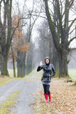 Woman in autumnal alley. Woman wearing rubber boots in autumnal alley Stock Photography