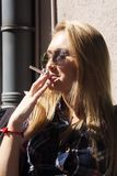 Woman in Avaiator Sunglasses Smoking a Cigarette Stock Images