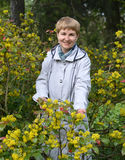 The woman of average years costs among the blossoming bushes of a trailing mahonia Royalty Free Stock Images
