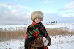 The woman of average years in a fur cap and a colorful shawl costs on the bank of the winter lake Royalty Free Stock Photo