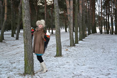 The woman of average years in a fur coat costs in the young pine wood Stock Photography