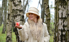 The woman of average years keeps in a hat on a palm decorative apple Stock Photo