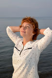 The woman of average years pensively looks into the sky, having thrown hands for the head Stock Photo
