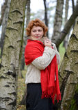 The woman of average years in a red stole costs among birches in. The wood Royalty Free Stock Images