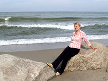 The woman of average years sits on a boulder. Coast of the Balti Stock Photography