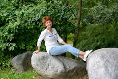 The woman of average years sits on a boulder in the park Stock Photography