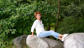 The woman of average years sits among huge boulders in the park Stock Images