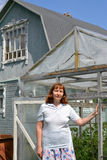 The woman of average years stands near the greenhouse Royalty Free Stock Image