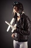 Woman in aviator hat standing with toy airplane in hand Stock Photos