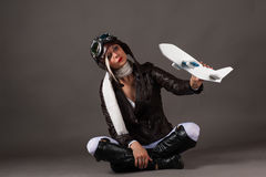 Woman in aviator helmet playing with toy airplane Stock Photography