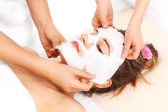 Woman aving a facial mask applied Stock Photography