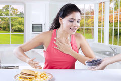 Woman avoid junk food and choose blueberry Stock Photos