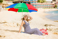 Woman awaiting for baby relaxing on the beach at hot sunny day Royalty Free Stock Image