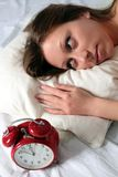 Woman awake with alarm clock Royalty Free Stock Image