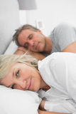 Woman awake as her partner is sleeping in bed Stock Photo