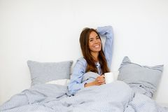 Woman awake in bed with cup of coffee Stock Images