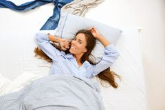 Woman awake in bed and smiling Stock Image