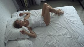 Woman awakening in comfortable cozy bed stretching and gets up. Young woman awakening in comfortable cozy bed stretching and gets up. Top view stock video